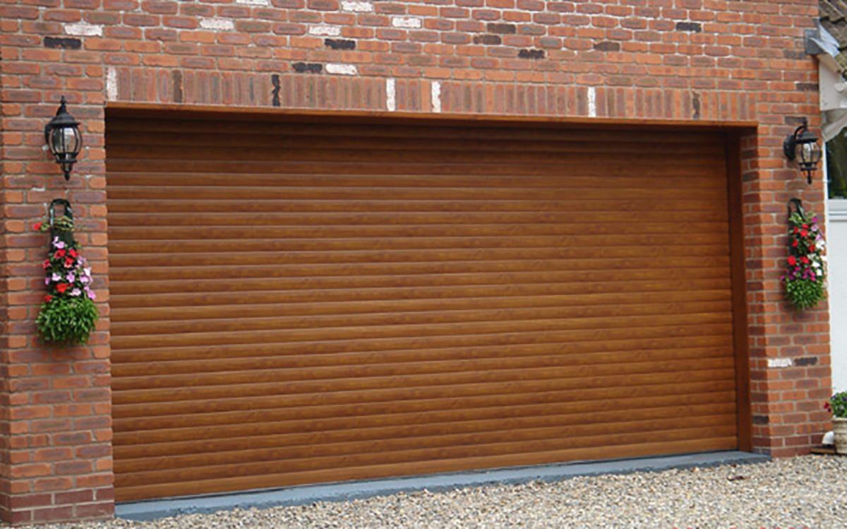 Double-width-golden-oak-garage-doors-on-gravel-driveway