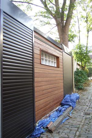 Two-Black-Gloss-shutter-doors-on-modern-timber-building